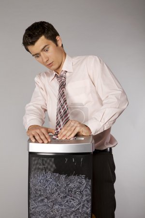 Photo for Young caucasian businessman with tie trapped in shredded machine - Royalty Free Image