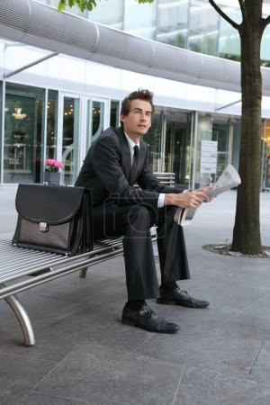 Photo for Young caucasian businessman reading newspapper in office exterior - Royalty Free Image