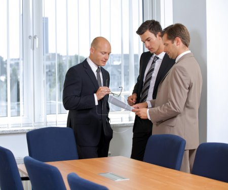 Photo for Three Businessmen talking in conference room - Royalty Free Image