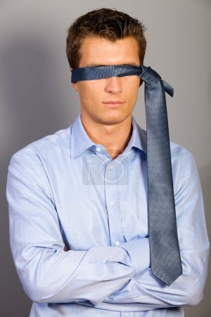 Businessman blindfolded with tie