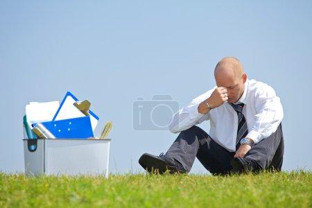 Businessman sitting next to basket
