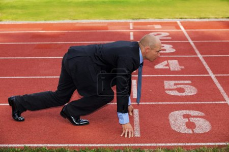 Photo for Businessman at the start line of running track - Royalty Free Image