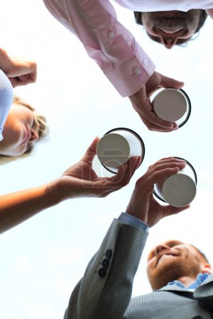 businesspeople holding disposable cups