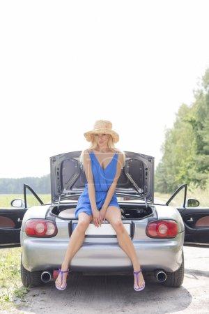 Photo pour Portrait complet de femme assise sur un tronc convertible contre un ciel dégagé - image libre de droit
