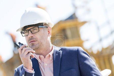 Photo pour Superviseur masculin utilisant walkie-talkie sur le chantier de construction - image libre de droit