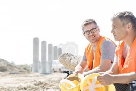 Photo for Smiling supervisor sitting with colleague at construction site - Royalty Free Image