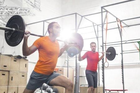Men lifting barbells