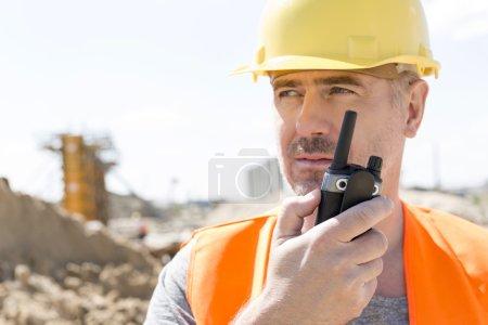 Photo pour Superviseur confiant utilisant talkie-walkie sur le chantier de construction - image libre de droit
