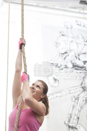 Photo pour Déterminé la femme corde en crossfit gym d'escalade - image libre de droit