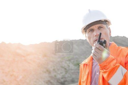 Photo pour Superviseur confiant utilisant talkie-walkie sur le chantier de construction contre ciel clair - image libre de droit