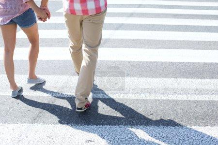 Photo pour Section basse du couple marchant sur le passage piétonnier - image libre de droit