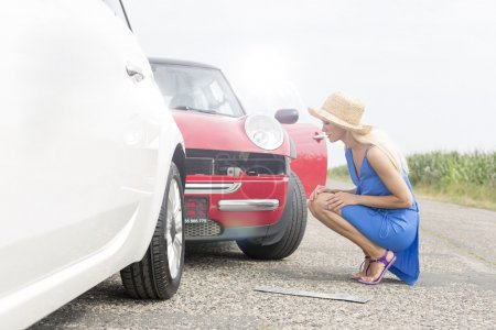 woman looking at damaged cars