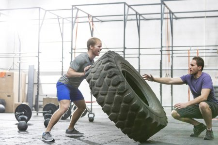 Photo for Man assisting at dedicated friend in flipping tire at crossfit gym - Royalty Free Image