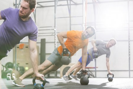 Men exercising with kettlebells