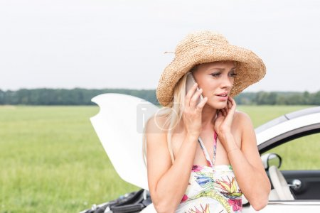 Photo for Frustrated woman using cell phone by broken down car - Royalty Free Image