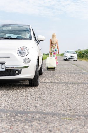 Photo for Rear view of woman with luggage leaving broken down car on country road - Royalty Free Image