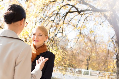 Photo for Businesswomen conversing in park on sunny day - Royalty Free Image
