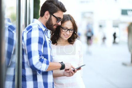 Smiling couple using smart phone