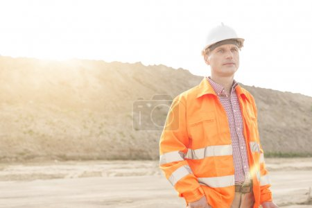 Photo pour Superviseur masculin réfléchi regardant ailleurs sur le chantier de construction - image libre de droit