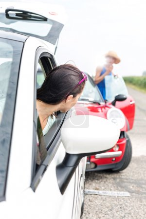 Woman looking at female crashing car