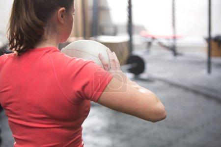 Photo pour Vue arrière de la femme tenant le médecine-ball en crossfit gym - image libre de droit