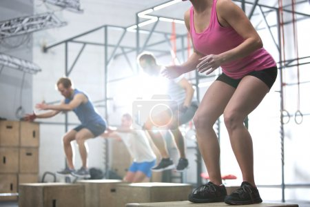 Photo for People doing box jump exercise in crossfit gym - Royalty Free Image