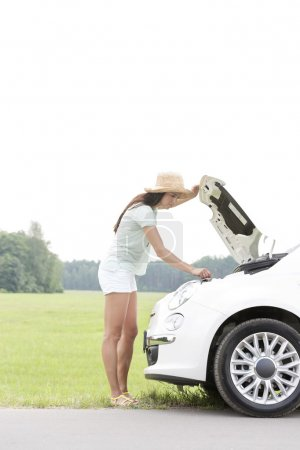 woman examining broken down car