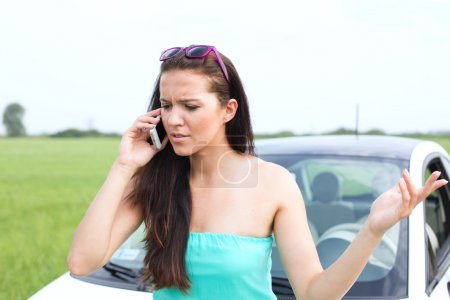 Photo for Frustrated woman using cell phone against broken down car - Royalty Free Image