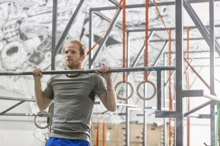 Photo for Confident man doing chin-ups in crossfit gym - Royalty Free Image