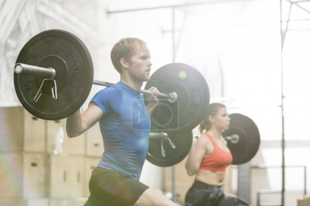Man and woman lifting barbells
