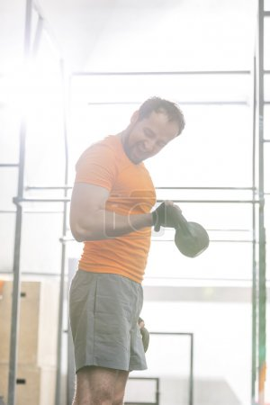 Photo pour Homme confiant kettlebell de levage dans le gymnase de crossfit - image libre de droit
