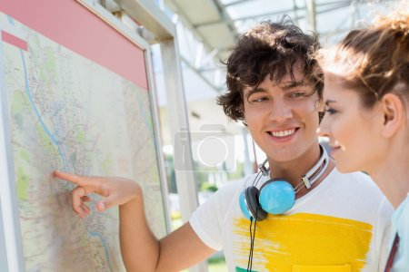 Happy man showing places on map