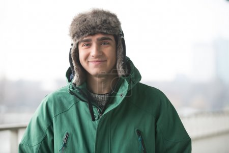 man in winter wear smiling