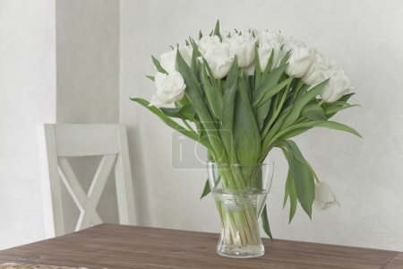 Vase with white tulips on a table