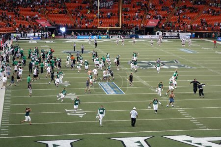 University of Hawaii players and fans rush on the field to celeb