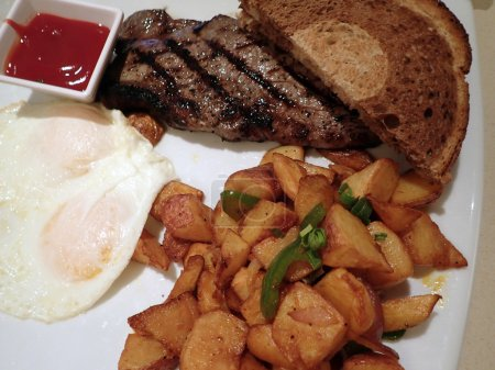 Steak with two eggs over easy, two slices of rye bread, potatos