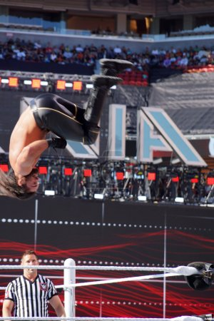 WWE Wrestler Seth Rollins flips in the air off top of the ropes