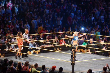 NXT Female wrestlers Charlotte Flair stands in ring with arms ex