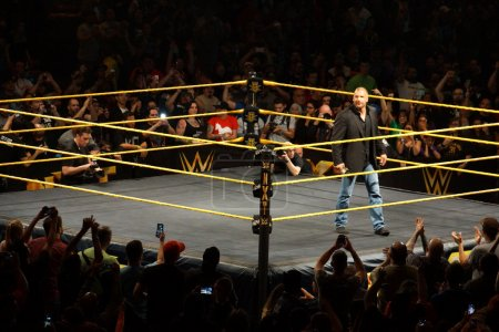WWE Superstar Legend Triple H smiles a smirk as he stands in the