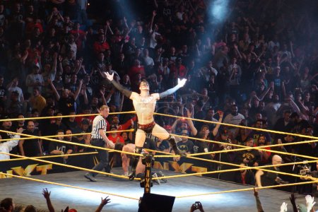 NXT male wrestler Finn Balor opens arms as he stands on ropes wh
