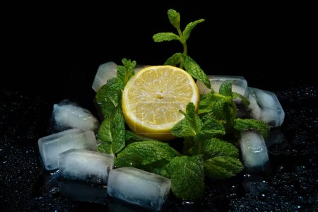 Photo for Lemon with mint and ice in a spray of water on a black background - Royalty Free Image