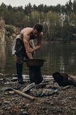 Zlatokop neoholený myje ruce u jezera s skalnatá stráň
