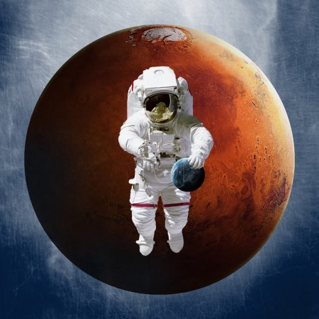 Astronaut, holding a planet Earth in hand on against of Mars