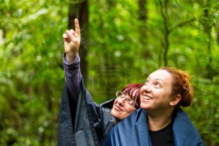 Photo pour Groupe de deux femmes touristiques adultes dans la jungle pointant vers le coin supérieur gauche - image libre de droit
