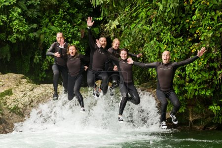 Group Of Adult People Jumping Into Small Waterfall
