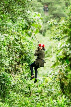 Photo pour Femme Afro Slim adulte sur tyrolienne dans la forêt équatorienne est proche de Baños De Agua Santa - image libre de droit