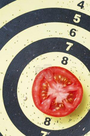 Photo pour Fléchettes cible avec tranche de tomate rouge fraîche au centre - image libre de droit