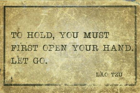 Photo pour Pour tenir, il faut d'abord ouvrir la main - citation de l'ancien philosophe chinois Lao Tzu imprimée sur du gros caroube vintage - image libre de droit
