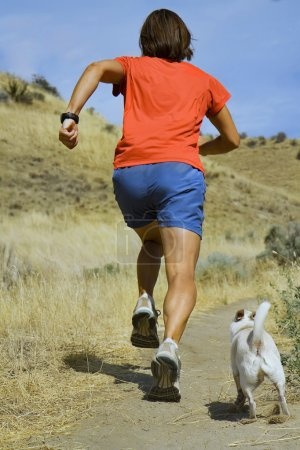 Photo for A girl running with her little white dog - Royalty Free Image