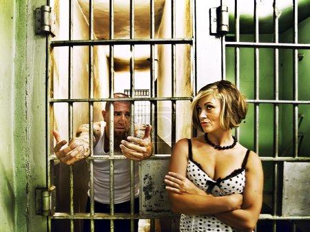 Photo pour Un homme expliquant quelque chose à une femme en prison - image libre de droit